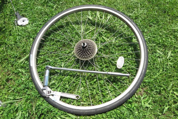 車体から分離した後輪と、ロングスピンナーハンドルとモンキーレンチ